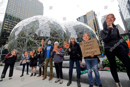 """Demonstrators hold images of Amazon CEO Jeff Bezos near their faces during a Halloween-themed protest at Amazon headquarters over the company's facial recognition system, """"Rekognition,"""", in Seattle. Protesters said that they were there in support of hundreds of Amazon employees who have signed a letter asking the company to stop marketing their facial recognition software to ICE and to drop its contract with software company Palantir and to law enforcement agencies"""