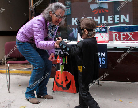 Democratic U.S. House candidate Kathleen Williams of Montana hands out Halloween candy to a child, in Helena, Mont. Williams is trying to defeat Republican Rep. Greg Gianforte in Tuesday's election