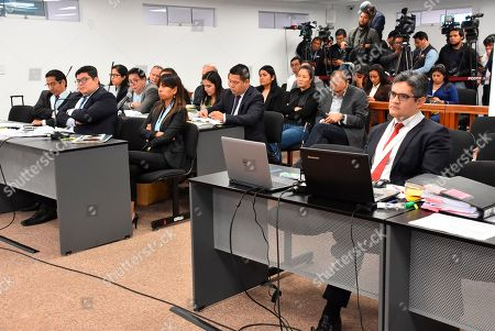 In this photo provided by Peru's Supreme Court communications office, former Peruvian first daughter Keiko Fujimori, top center with her arms folded, sits in court where Judge Richard Concepcion ruled that she should be detained as a preventative measure while prosecutors investigate allegations she led a criminal network within her party that received about $1 million in payments from Brazilian construction giant Odebrecht, in Lima, Peru, . Keiko Fujimori denies she accepted money from Odebrecht during her 2011 presidential run and has called the investigation a political witch hunt