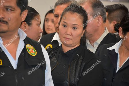In this photo provided by Peru's Supreme Court communications office, former Peruvian first daughter Keiko Fujimori stands in court where Judge Richard Concepcion ruled that she should be detained as a preventative measure while prosecutors investigate allegations she led a criminal network within her party that received about $1 million in payments from Brazilian construction giant Odebrecht, in Lima, Peru, . Keiko Fujimori denies she accepted money from Odebrecht during her 2011 presidential run and has called the investigation a political witch hunt