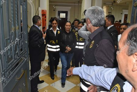In this photo provided by Peru's Supreme Court communications office, former Peruvian first daughter Keiko Fujimori is lead to jail in handcuffs after Judge Richard Concepcion ruled that she should be detained as a preventative measure while prosecutors investigate allegations she led a criminal network within her party that received about $1 million in payments from Brazilian construction giant Odebrecht, in Lima, Peru, . Keiko Fujimori denies she accepted money from Odebrecht during her 2011 presidential run and has called the investigation a political witch hunt