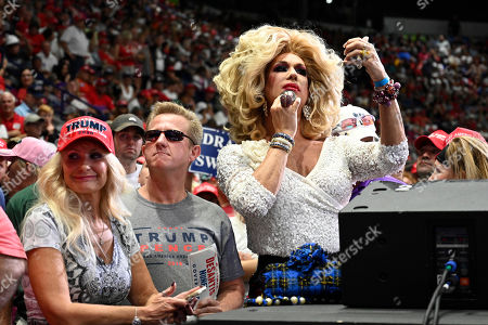 Elaine Lancaster of Miami, right, waits for President Donald Trump to speak at a rally in Estero, Fla., . Trump is campaigning for Florida Republican Gov. Rick Scott, who is challenging incumbent Democratic Sen. Bill Nelson for a seat in the Senate