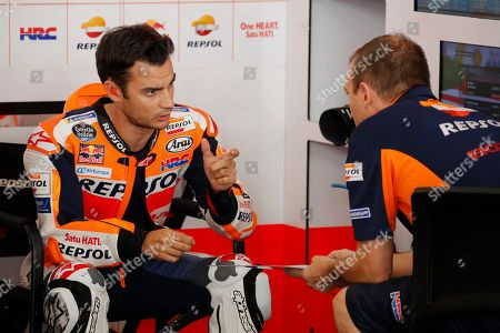 Honda rider Dani Pedrosa of Spain, left, talks with his mechanic inside his team garage during the second free practice ahead of Malaysia MotoGP at Sepang International circuit in Sepang, Malaysia