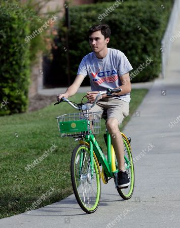 David Hogg, a student who survived the Stoneman Douglas High School shooting rides a bike on the campus of the University of Central Florida encouraging students to vote during a Vote for Our Lives event at the University of Central Florida in Orlando, Fla. Nine months after 17 classmates and teachers were gunned down at their Florida school, Parkland students are finally facing the moment they've been leading up to with marches, school walkouts and voter-registration events throughout the country: their first Election Day