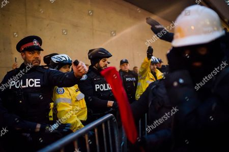 Police pepper spray protesters as they clash prior to a Toronto Munk debate featuring former White House chief strategist Steve Bannon and conservative commentator David Frum in Toronto on . The debate played out just ahead of the fiercely contested midterm congressional elections in the United States on Nov. 6