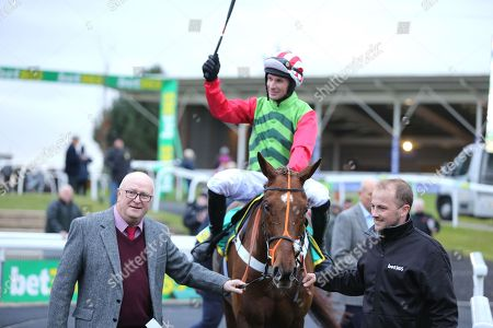 Stock Photo of DEFINITLY RED (1) ridden by Danny Cook and trained by Brian Ellison  enter the Winners Enclosure with happy Owner Phil Martin after winning The Class 1 bet365 Charlie Hall Steeple Chase over 3m (£100,000) during the Bet365 Meeting at Wetherby Racecourse, Wetherby. Picture by Mick Atkins