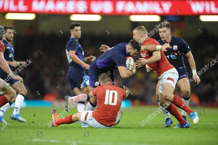 Alex Dunbar of Scotland is tackled by Gareth Anscombe and Hadleigh Parkes of Wales