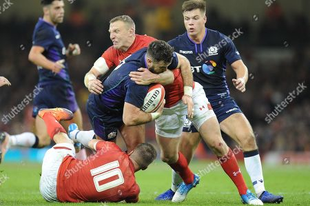 Alex Dunbar of Scotland  is tackled by Gareth Anscombe of Wales and Hadleigh Parkes of Wales