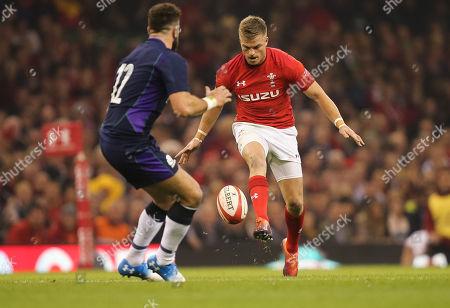 Gareth Anscombe of Wales  kicks past Alex Dunbar of Scotland