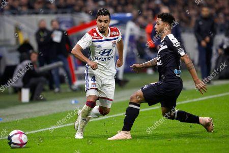 Lyon's Rafael Pereira Da Silva, left, challenges for the ball with Bordeaux' Otavio Passos Santos during their French League One soccer match in Decines, near Lyon, central France