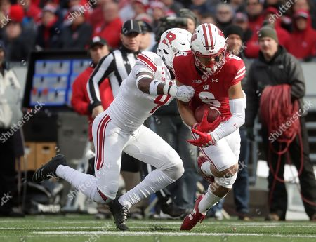 Wisconsin's Danny Davis III catches a pass in front of Rutgers's Saquan Hampton during the first half of an NCAA college football game, in Madison, Wis