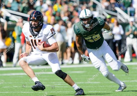 Stock Image of Baylor Bears defensive end Greg Roberts (52) tries to tackle Oklahoma State Cowboys quarterback Taylor Cornelius (14) during the 2nd half of the NCAA Football game between the Oklahoma State Cowboys and the Baylor Bears at McLane Stadium in Waco, Texas