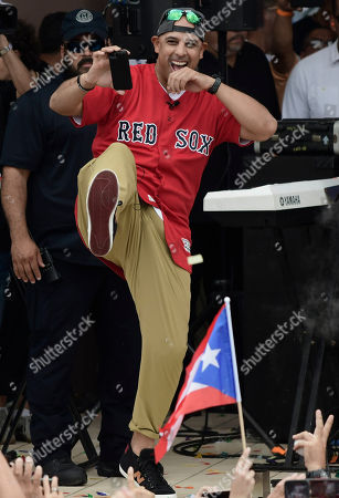 Boston Red Sox manager Alex Cora celebrates on a stage at his hometown with the 2018 World Series trophy, accompanied by several players and coaches, including Chairman Tom Werner and President and CEO Sam Kennedy, in Caguas, Puerto Rico