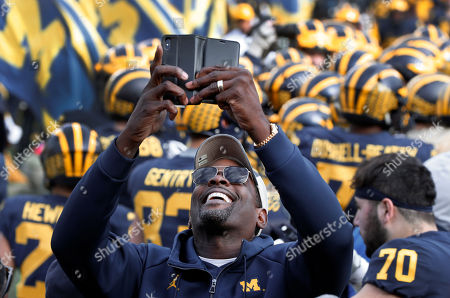 Chris Webber, a former Michigan basketball player, smiles while recording on the sidelines before an NCAA college football game against the Penn State in Ann Arbor, Mich