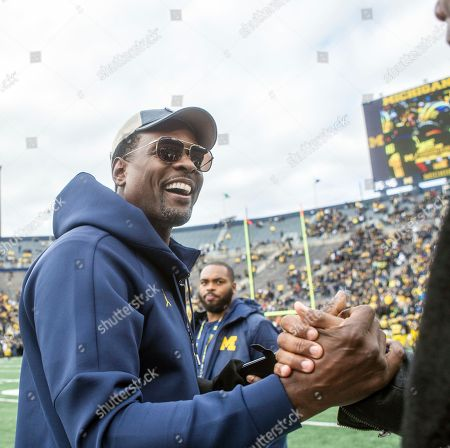 Stock Picture of Former Michigan basketball player Chris Webber, right, greet fans on the Michigan Stadium field prior to an NCAA college football game against Penn State in Ann Arbor, Mich., . Michigan is making Webber an honorary captain for the game