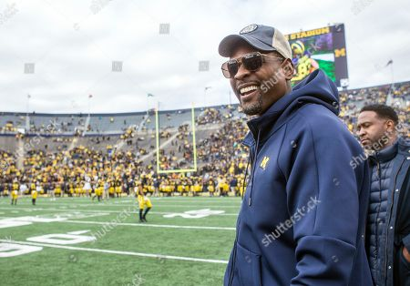 Former Michigan basketball player Chris Webber, right, watch pregame warmups on the Michigan Stadium field prior to an NCAA college football game against Penn State in Ann Arbor, Mich., . Michigan is making Webber an honorary captain for the game
