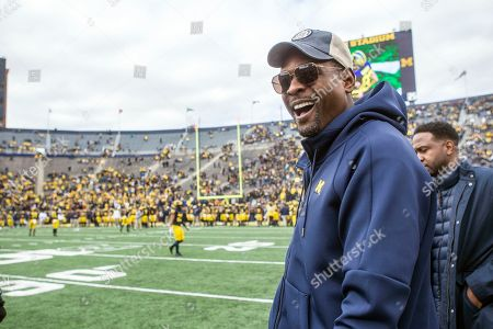 Stock Photo of Former Michigan basketball player Chris Webber, right, watch pregame warmups on the Michigan Stadium field prior to an NCAA college football game against Penn State in Ann Arbor, Mich., . Michigan is making Webber an honorary captain for the game