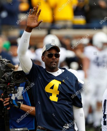 Stock Image of Chris Webber, a former Michigan basketball player, waves before an NCAA college football game against Penn State in Ann Arbor, Mich