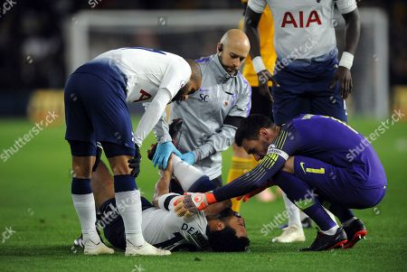 Tottenham's Mousa Dembele, center, receives medical help during the English Premier League soccer match between Wolverhampton Wanderers and Tottenham Hotspur at the Molineux Stadium in Wolverhampton, England