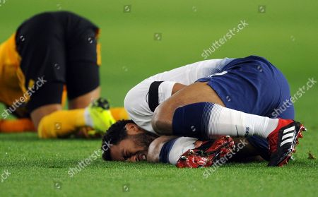 Tottenham's Mousa Dembele, right, lies on the pitch during the English Premier League soccer match between Wolverhampton Wanderers and Tottenham Hotspur at the Molineux Stadium in Wolverhampton, England