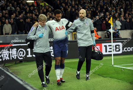 Medics help Tottenham's Mousa Dembele, center, to leave the field during the English Premier League soccer match between Wolverhampton Wanderers and Tottenham Hotspur at the Molineux Stadium in Wolverhampton, England