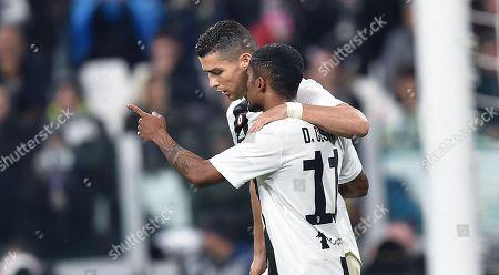 Juventus' Cristiano Ronaldo (L) and Douglas Costa celebrate after the owngoal of Cagliari's Filip Bradaric during the Italian Serie A soccer match Juventus FC vs Cagliari Calcio at Allianz Stadium in Turin, Italy, 03 November 2018.