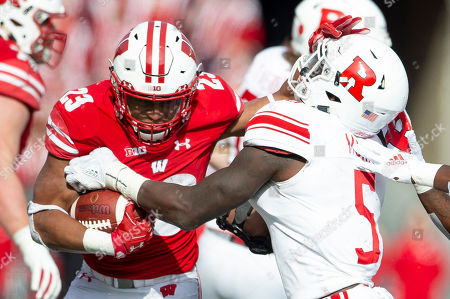 Wisconsin Badgers running back Jonathan Taylor #23 stiff arms Rutgers Scarlet Knights linebacker Trevor Morris #5 during the NCAA Football game between the Rutgers Scarlet Knights and the Wisconsin Badgers at Camp Randall Stadium in Madison, WI. Wisconsin defeated Rutgers 31-17