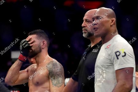 Chris Weidman, left, reacts before the official ruling after he lost to Ronaldo Souza, right, in a middleweight mixed martial arts bout at UFC 230, at Madison Square Garden in New York