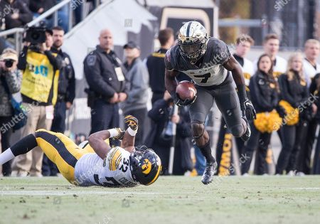 Iowa linebacker Djimon Colbert (32) trips up Purdue wide receiver Isaac Zico (7) during NCAA football game action between the Iowa Hawkeyes and the Purdue Boilermakers at Ross-Ade Stadium in West Lafayette, Indiana. Purdue defeated Iowa 38-36