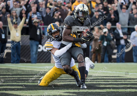 Purdue wide receiver Isaac Zico (7) catches the ball for a touchdown as Iowa defensive back Julius Brents (20) defends during NCAA football game action between the Iowa Hawkeyes and the Purdue Boilermakers at Ross-Ade Stadium in West Lafayette, Indiana. Purdue defeated Iowa 38-36