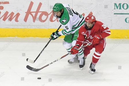 North Dakota Fighting Hawks forward/defenseman Casey Johnson (5) and Wisconsin Badgers forward Jarod Zirbel (28) fight for the puck during a NCAA men's college hockey game between the Wisconsin Badgers and the University of North Dakota Fighting Hawks at Ralph Engelstad Arena in Grand Forks, ND. North Dakota won 3-2 in overtime