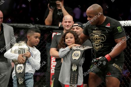 Stock Image of Daniel Cormier, right, lets his kids, Daniel, left, and Marquita, hold his championship belts after he defeated Derrick Lewis by submission in the second round of a heavyweight mixed martial arts bout at UFC 230, early, at Madison Square Garden in New York