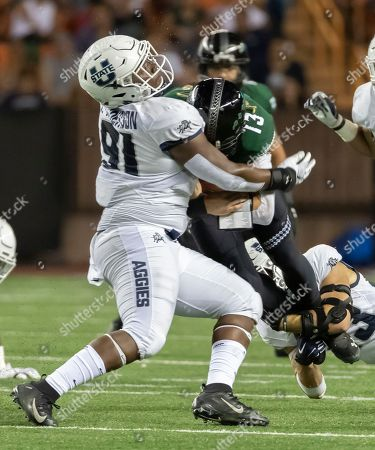 Utah State defensive end Devon Anderson (91) and his teammate safety Gaje Ferguson, bottom right, sack Hawaii quarterback Cole McDonald (13) in the first half of an NCAA college football game, in Honolulu