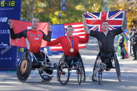 Daniel Romanchuk, Marcel Hug, of Great Britain pose for a picture. Second place finisher Marcel Hug of Switzerland, left, first place finisher Daniel Romanchuk of the United States, center, and third place finisher David Weir of Great Britain pose for a picture at the finish line of the New York City Marathon in New York