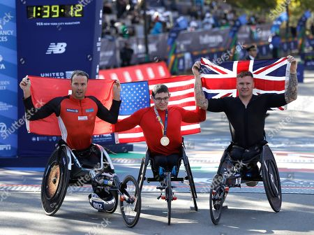 (L-R) Marcel Hug of Switzerland, 2nd place finisher Daniel Romanchuk, winner from the United States and David Weir of the United Kingdom raise their flags after the Men's Wheelchair race of the 2018 New York City Marathon, in New York, USA, 04 October 2018.