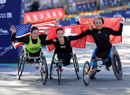 (L-R) Tatyana McFadden of the United States, the 2nd place finisher, Manuela Schaer, winner from Switzerland and Lihong Zou of China raise their flags after the Women's Wheelchair race of the 2018 New York City Marathon, in New York, USA, 04 October 2018.