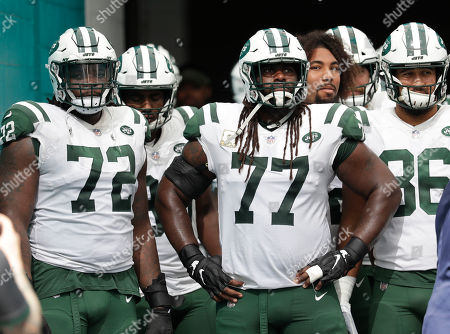 Stock Image of New York Jets offensive tackle Brandon Shell (72), New York Jets offensive guard James Carpenter (77) wait to enter the field before an NFL football game, in Miami Gardens, Fla
