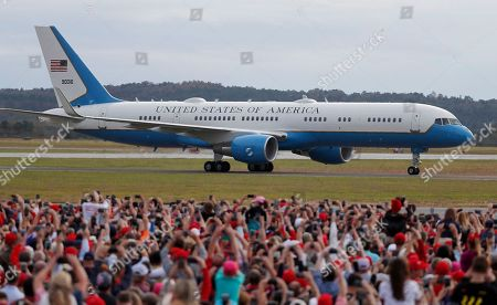 Air Force One taxis past a large crowd as President Donald Trump arrives for during a rally for Georgia Republican gubernatorial candidate Brian Kemp, in Macon, Ga