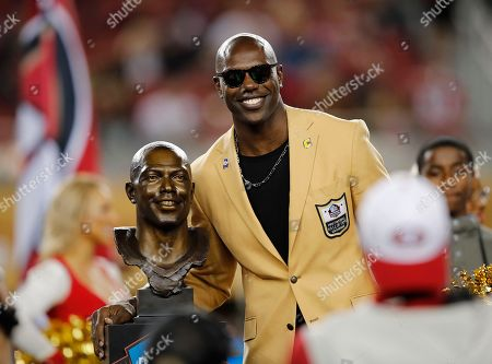 Former NFL wide receiver Terrell Owens poses next to his Pro Football Hall of Fame bust during halftime of an NFL football game between the San Francisco 49ers and the Oakland Raiders in Santa Clara, Calif