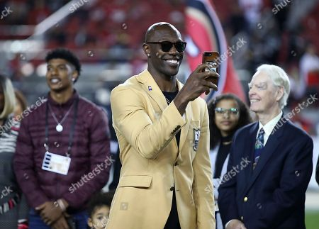 Former NFL wide receiver Terrell Owens holds up his phone during a ceremony to receive his Pro Football Hall of Fame ring during halftime of an NFL football game between the San Francisco 49ers and the Oakland Raiders in Santa Clara, Calif