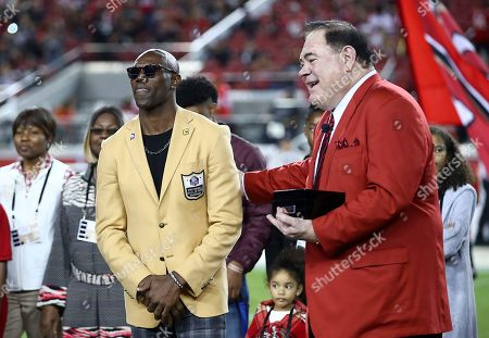 Former NFL wide receiver Terrell Owens, left, stands next to Pro Football Hall of Fame president David Baker during halftime of an NFL football game between the San Francisco 49ers and the Oakland Raiders in Santa Clara, Calif
