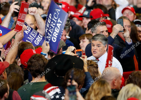 Television personality Sean Hannity speaks to members of the audience while signing autographs before the start of a campaign rally, in Cape Girardeau, Mo