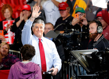 Television personality Sean Hannity waves as members of the audience cheer before the start of a campaign rally, in Cape Girardeau, Mo