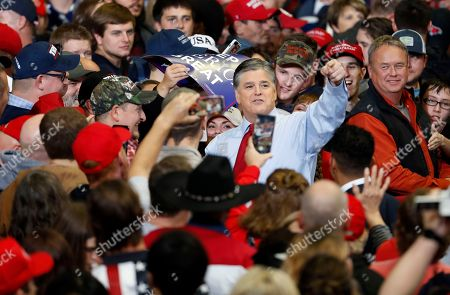 Television personality Sean Hannity points as he meets with members of the audience before the start of a campaign rally, in Cape Girardeau, Mo., with President Donald Trump