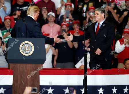 President Donald Trump shakes hands with Fox News Channel's Sean Hannity, right, during a campaign rally, in Cape Girardeau, Mo