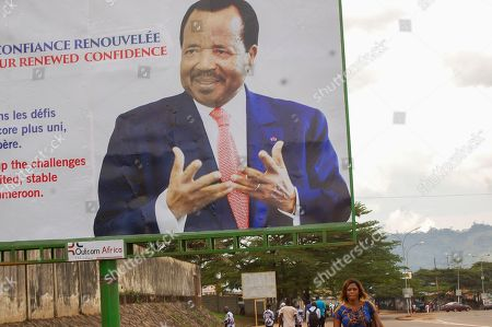 Cameroonians walk under a billboard with the image of president Paul Biya after witnessing his swearing in as President of Cameroon for a seventh term in Yaounde, Cameroon 06 November 2018. Aged 86 Paul Biya was sworn in after 36 years in power for a consecutive seventh term in office after being declared winner of October 7 presidential election by the Constitutional Council.