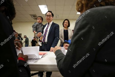 Andy Kim, the Democratic candidate in New Jersey's third Congressional District, holds his son as he stands with his wife Kammy Lai and their son as they prepare to vote, in Bordentown, N.J. Kim is facing Tom MacArthur, the Republican incumbent candidate in New Jersey's third Congressional District