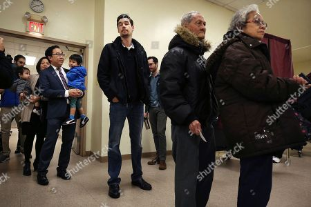 Andy Kim, third from right, the Democratic candidate in New Jersey's third Congressional District, holds his son, as he stands with his wife Kammy Lai (behind) and their son as they wait in line to vote, in Bordentown, N.J. Kim is facing Tom MacArthur, the Republican incumbent candidate in New Jersey's third Congressional District