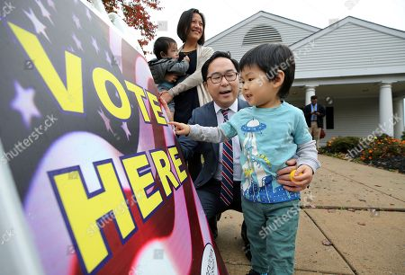 Andy Kim, the Democratic candidate in New Jersey's third Congressional District, plays a word-game with his son Austin Kim, as his wife Kammy Lai looks on with their son Ausgust Kim, outside a polling place, in Bordentown, N.J. Kim is facing Tom MacArthur, the Republican incumbent candidate in New Jersey's third Congressional District