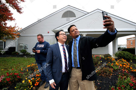 Stock Image of Greg Walker, right, takes a photograph with Andy Kim, the Democratic candidate in New Jersey's third Congressional District, after they voted, in Bordentown, N.J. Kim is facing Republican incumbent candidate Tom MacArthur
